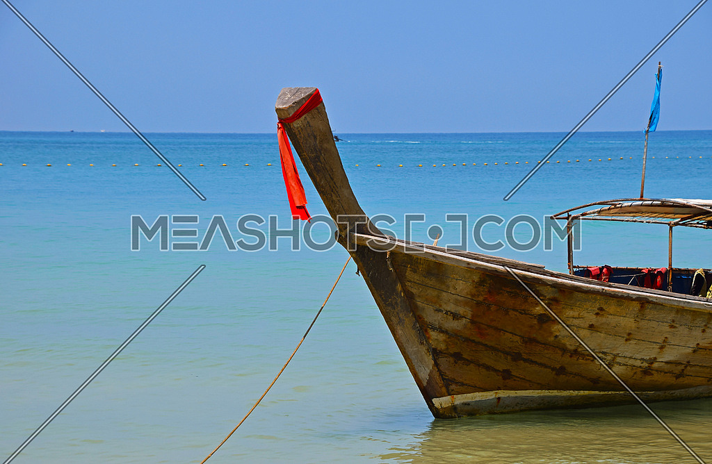 Traditional Thailand old vintage unpainted long tail boat in transparent turquoise water crossed with yellow float buoys