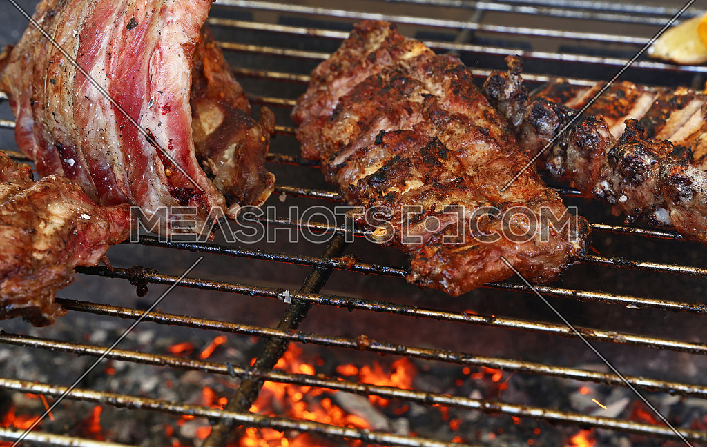 Several racks of pork spare ribs cooked on fire barbecue grill, close up, high angle view