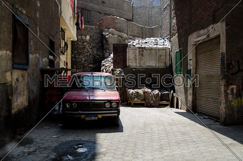 An old red car parked in an empty alley in Cairo at day