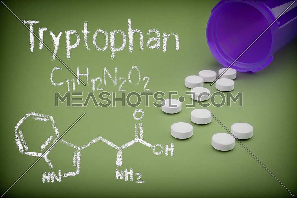 Pills spilling from an open bottle on green background, Chemical formulation of trytophan written with chalk, conceptual image