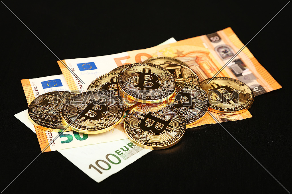 Close up heap of golden bitcoin physical coins on top of Euro paper banknotes isolated on black background with copy space, high angle view, selective focus
