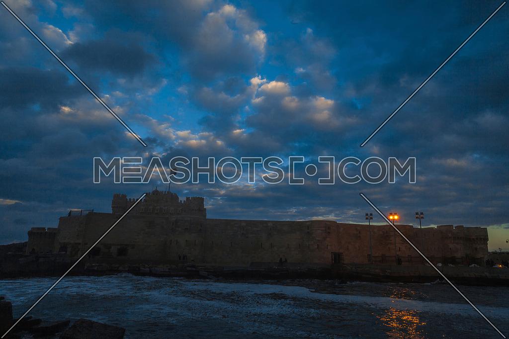 Long Shot outside Citadel of Qaitbay shows sea waves at Cloudy day to night
