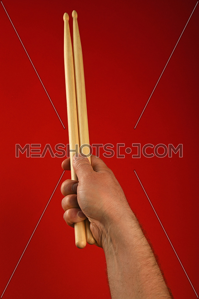 Man hand holding two wooden drumsticks over red background, point of view