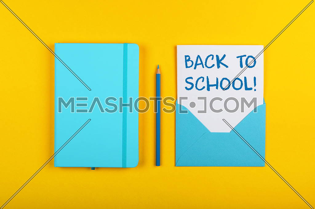 Back to school handwritten sign on white paper in blue envelope next to leather cover notebook over yellow paper background with copy space