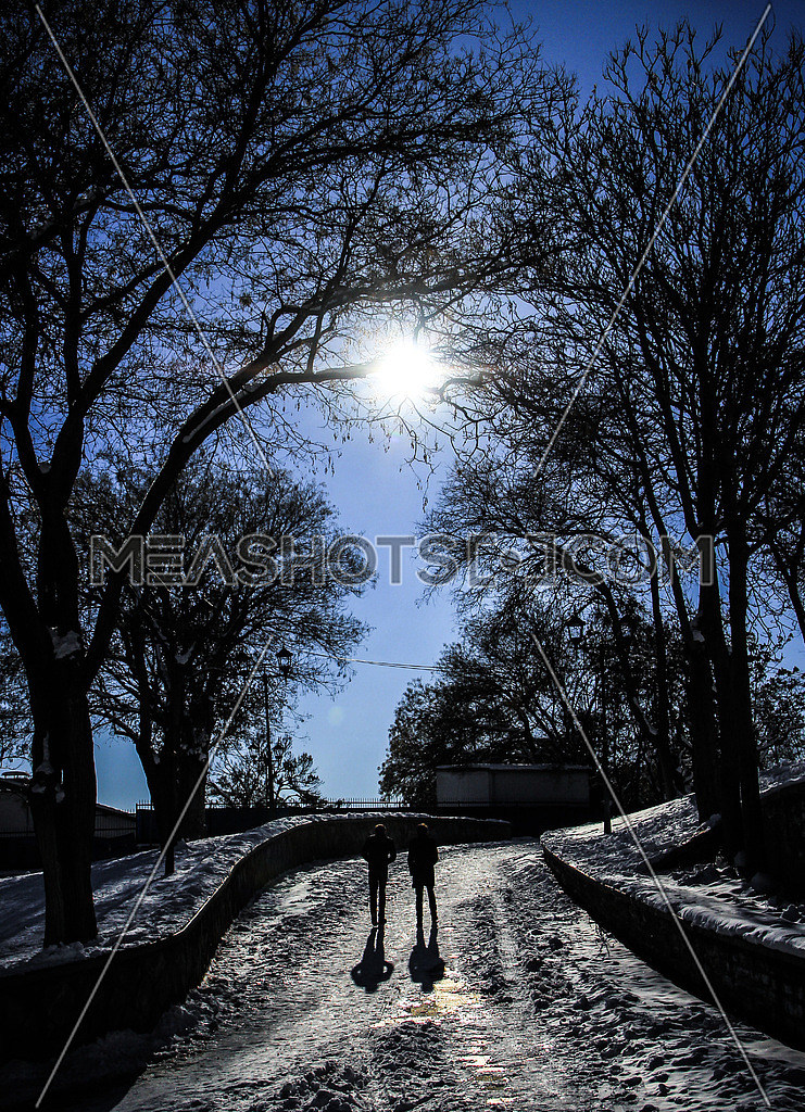 two people walking on a snow path