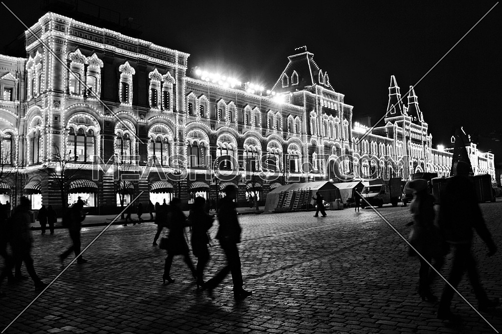black and white image of the Red Square in moscow at Night with people walking in the streets