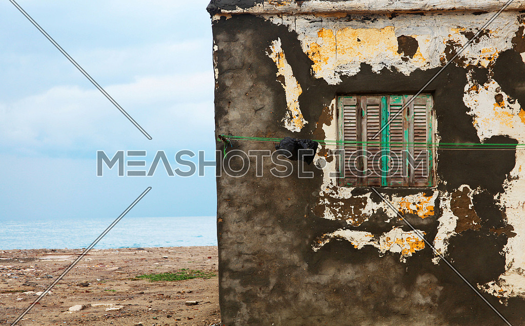 An old building by the sea with a closed shutter worn down due to humidity