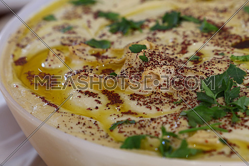 Close up of hummus, traditional Mediterranean and Middle Eastern dip or spread, with olive oil, green fresh parsley and chili pepper in a bowl, high angle view