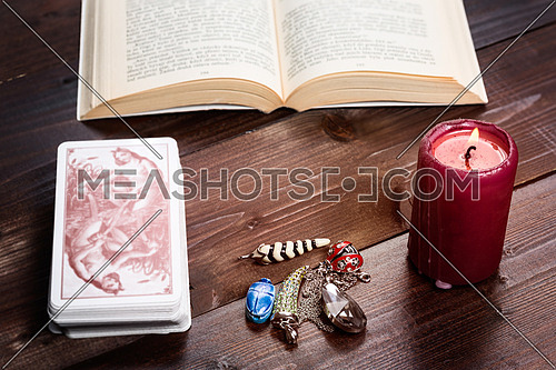 Composition of esoteric objects,candle,cards and book used for healing and fortune-telling.