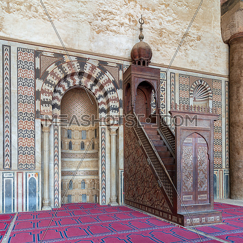 Colorful decorated marble wall with engraved niche (Mihrab) and wooden platform (Minbar) at the Mosque of Al Nasir Mohammad Ibn Qalawun, situated in the Citadel of Cairo in Egypt