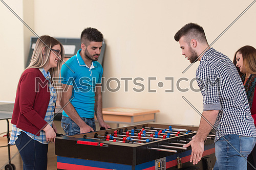 Group Of Young Men And Women Enjoying A Game Of Foosball