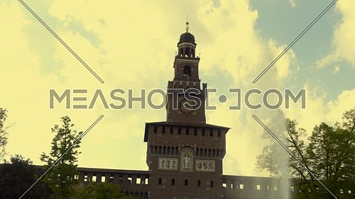 Main tower to the Sforza Castle - Castle Sforzesco and fountain in front of it, sunny day and clouds in the sky,Milan, Italy
