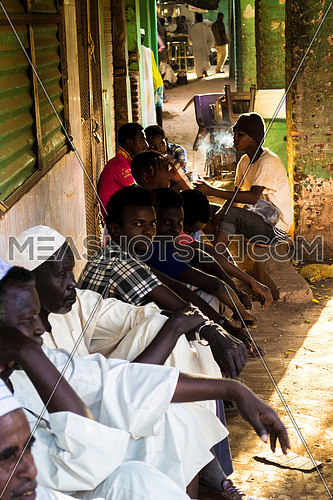 A group of sudanese men and boys sitting on the floor