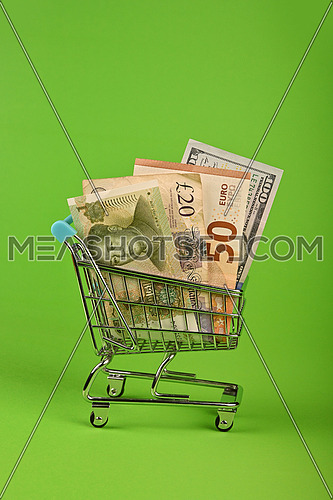 Close up several different world paper currency banknotes in small shopping cart over green background, low angle side view