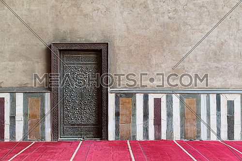 Old wall including a historic decorated bronzed door in an old mosque, Cairo, Egypt
