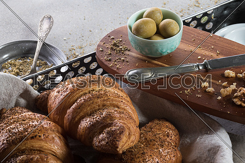 A tray of freshly baked croissant and a green bowl filled with green olives