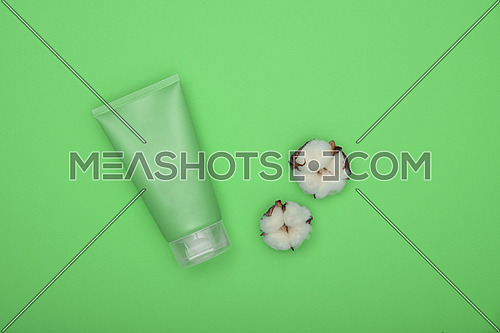 Close up one bottle of shower gel, shampoo or body care beauty product and white cotton flower over green background, elevated top view, directly above