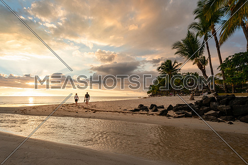 A couple walking on the beach at sunset, Flic en flac beach, mauritius island
