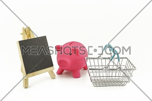 Pink pig saver, small chalk board and wire shopping basket isolated on a white background