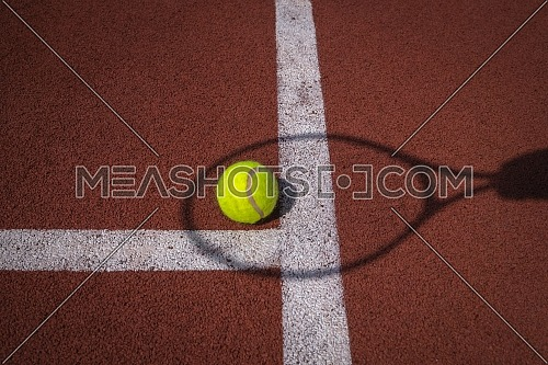 Shadows of net and racket surrounding a tennis ball on a white line on an outdoor court in sunshine in a sport and active lifestyle concept