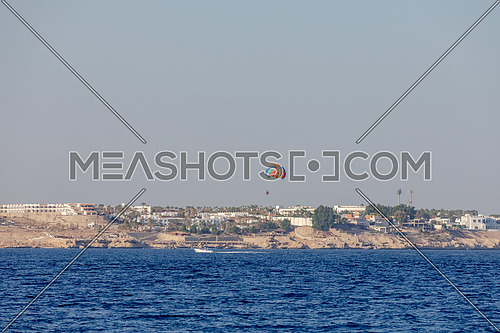 Long for tourist parasailing in the Red Sea showing Sharm el shaikh city by day