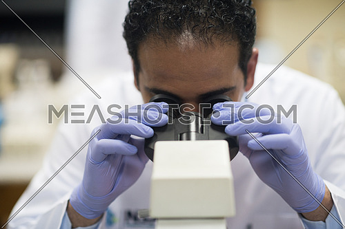 portrait of a young middle eastern man with a microscope in a large modern laboratories