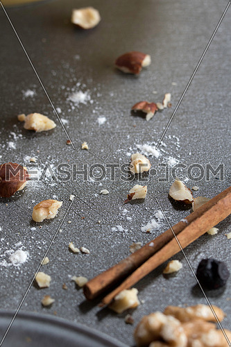 Dry nuts crumbs and flour on a grey background