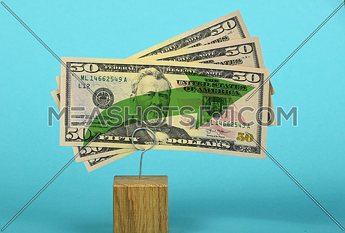 Growth and support of American economy and US dollar, tree fifty dollars banknote with green arrow up on two holders over blue background