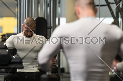 Portrait Of A Muscular Man Resting On The Bench In Fitness Gym