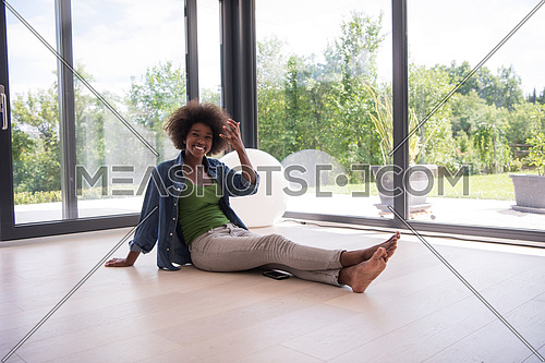 Beautiful african american young woman in casual fashion clothes sitting near window