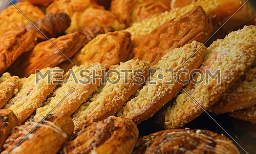 Selection of freshly baked golden brown sweet pastry cookies in retail bakery store display, close up, high angle view
