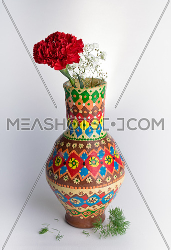 Still life composition of colorful pottery vase with one red flower and small white flowers on white background