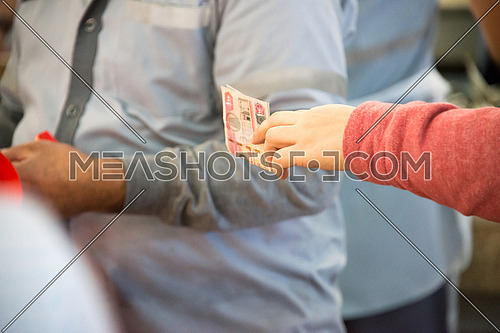 a lady paying for fish in Fish Market In Dubai