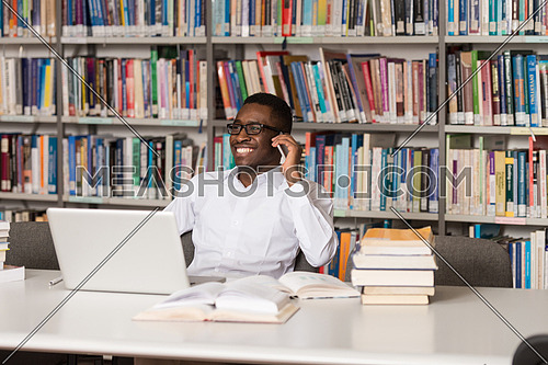 African Male Student Talking On The Phone In Library - Shallow Depth Of Field