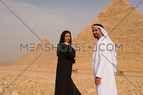 portrait of  Emiratie man and his wife as tourists at the pyramids