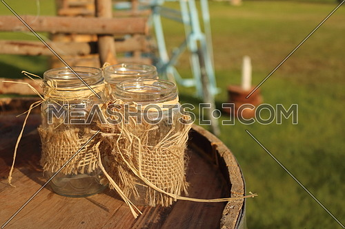 three glass jars stacked on wooden barrel
