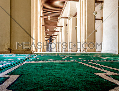 ElHakem Mosque with a man standing on the praying carpet