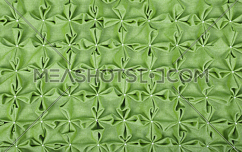 Close up background texture of green textile puffs for Canadian smocking upholstery decoration with beads