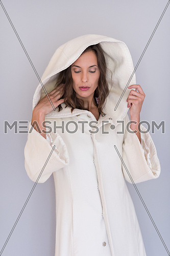portrait of Beautiful young woman wearing a white coat with hood isolated on white background