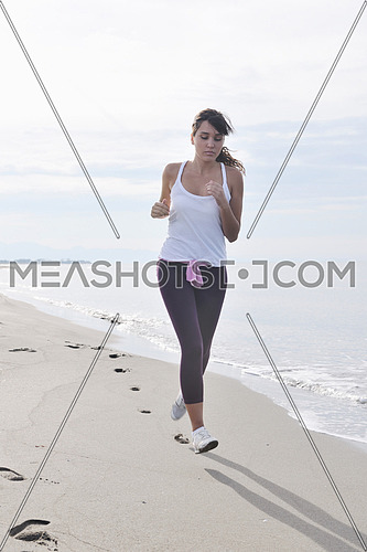 young healthy woman jogging and running at beach at early morning