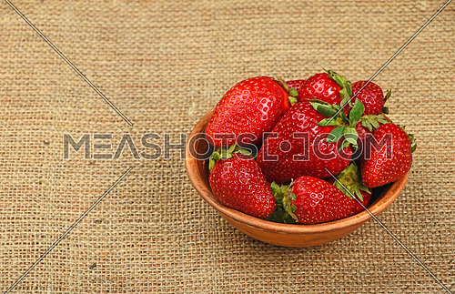 Mellow fresh red summer strawberries in rustic ceramic bowl on jute burlap canvas background, high angle view