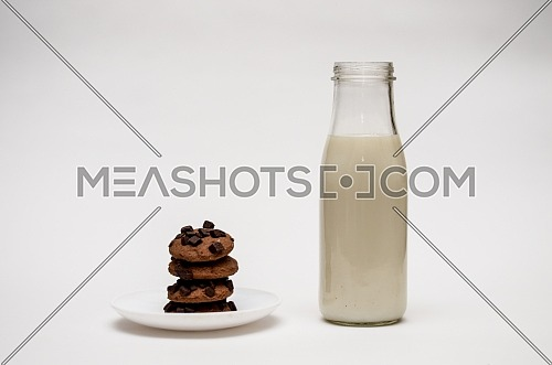 A glass bottle of milk and chocolate chips cookies