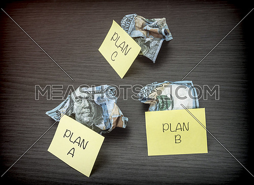 Failed business plan A, B and C, minted dollar banknotes on a wooden desk, conceptual  image