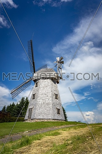 Old windmill in grassland in a country landscape under a cloudy blue sky in a scenic landscape
