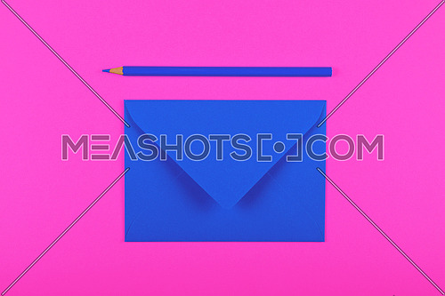 One closed blank indigo blue paper envelope and wooden pencil over vivid magenta pink background, flat lay, directly above