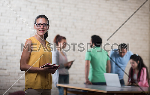 portrait of a young middle eastern informal business woman with a notebook in his hand and a smile