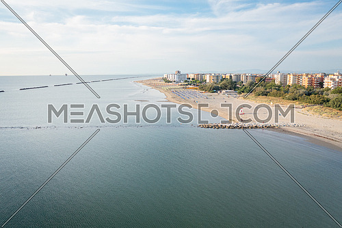 Drone shot of sandy beach with umbrellas,gazebos and town background.Summer vacation concept.Lido Adriano town,Adriatic coast, Emilia Romagna,Italy.