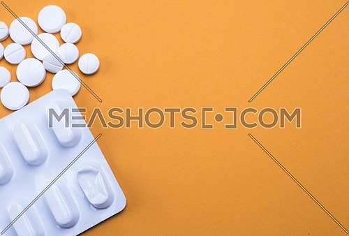 Blister and white tablets isolated on orange background, conceptual image