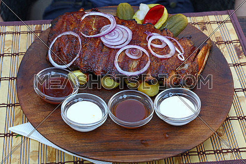Rack of grill roasted pork spare ribs with onion rings, pepper and sauces, close up, high angle view, personal, perspective