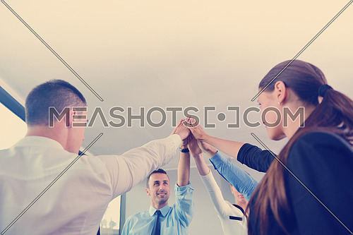 business people group joining hands and representing concept of friendship and teamwork,  low angle view